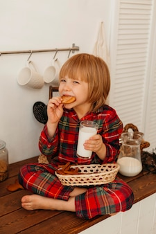 Mały chłopiec je świąteczne ciasteczka i pije mleko
