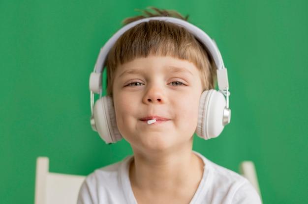 Mały chłopiec jedzenie lollipop ze słuchawkami