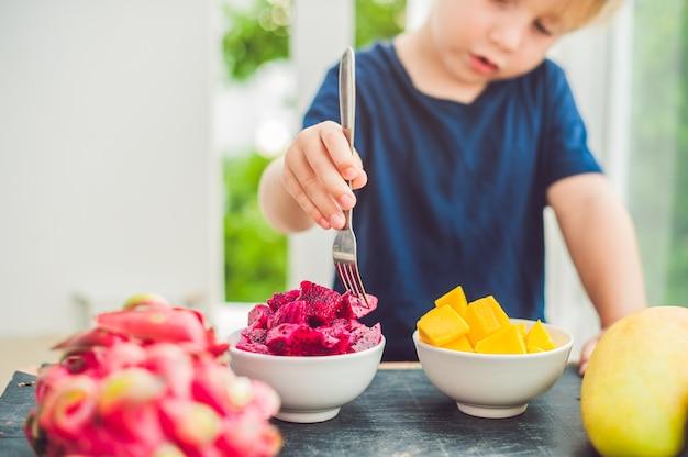 Mały chłopiec jedzenie owoców na tarasie