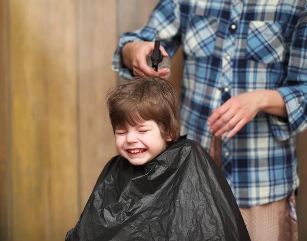 Mały chłopiec jest przycięty w jasnych emocjach fryzjera na twarzy
