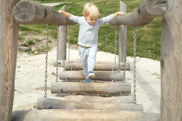 Mały chłopiec kaukaski blond grając na placu zabaw dla dzieci w słoneczny jesienny dzień.