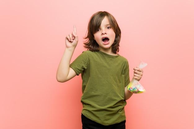 Mały chłopiec kaukaski gospodarstwa cukierki o jakiś świetny pomysł, kreatywności.