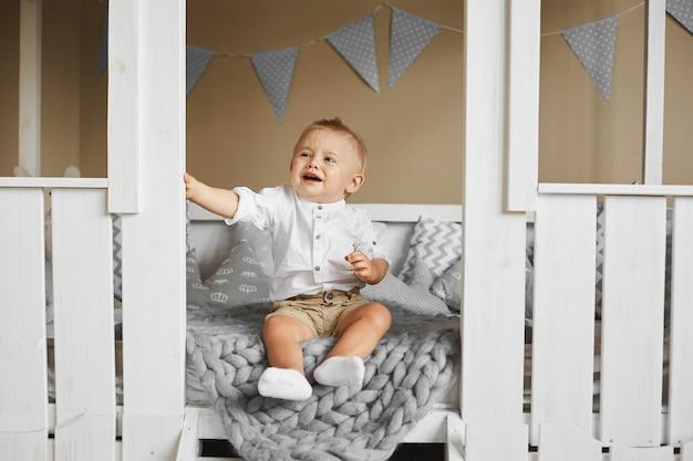 Mały chłopiec kaukaski płacze siedząc na kanapie we wnętrzu domu