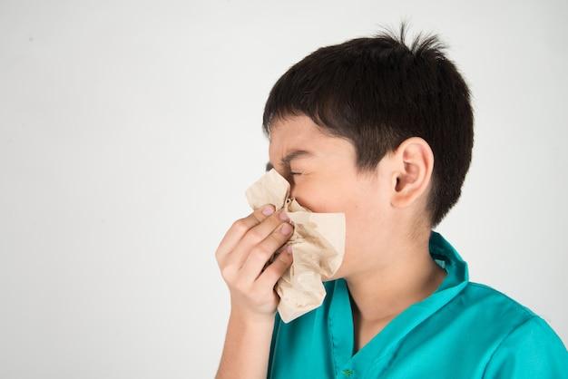 Mały chłopiec kicha i kaszle z grypy, używając tkanek do czyszczenia