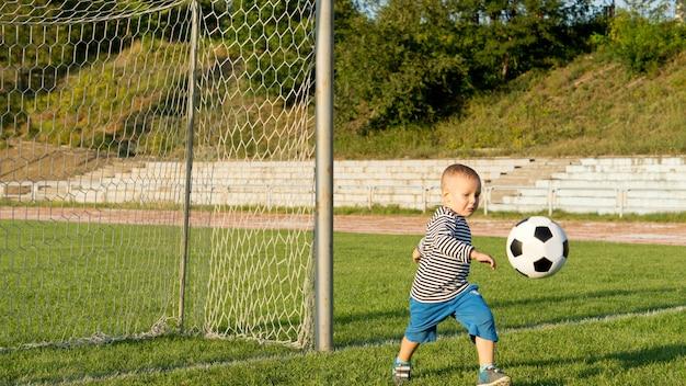 Mały chłopiec kopie piłkę nożną w zielonej trawie przed słupkami na boisku