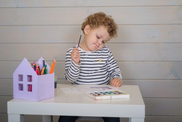 Mały chłopiec kręcone rysuje farby akwarelowe na papierze siedząc przy stole