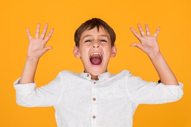 Mały chłopiec krzyczy z rękami w górze