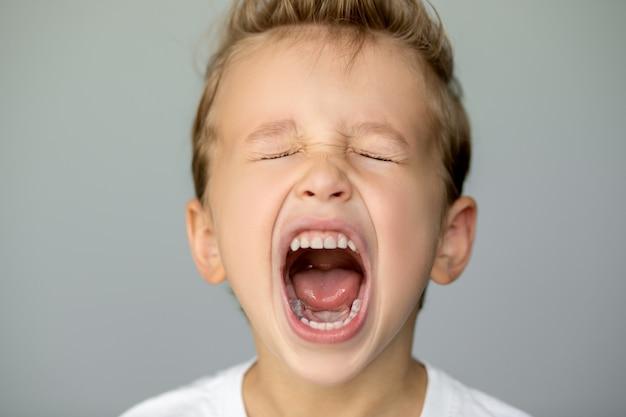 Mały chłopiec krzyczy z zamkniętymi oczami. wolnostojący młodzieniec na szarym tle otworzył szeroko usta, białe równe zęby