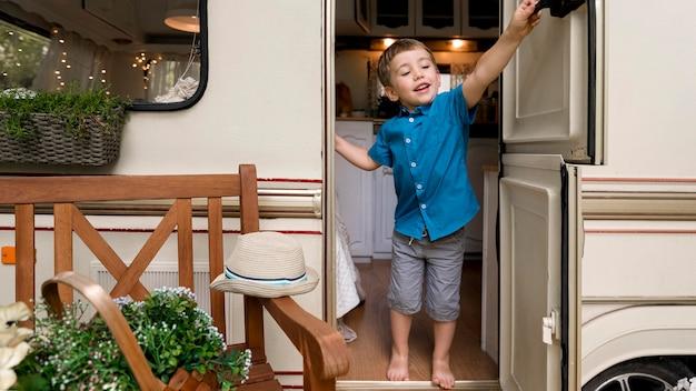 Mały chłopiec, który chce zamknąć drzwi przyczepy kempingowej
