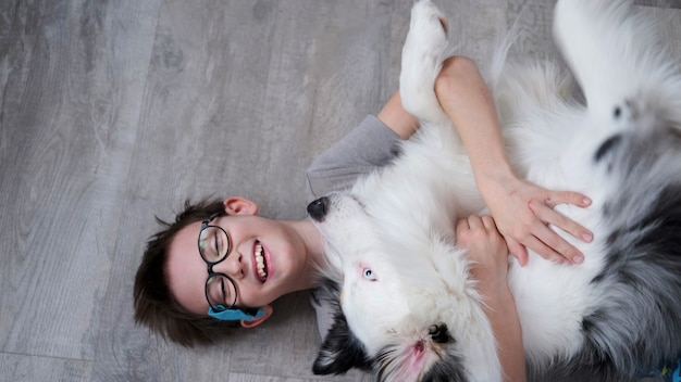 Mały chłopiec leżący i przytula psa owczarka australijskiego merle