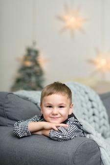 Mały chłopiec leży na kanapie pokrytej szarym dzianinowym kocem i uśmiecha się