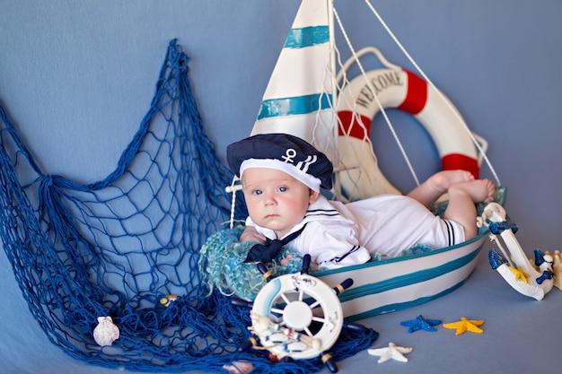 Mały chłopiec leży w łodzi w marynarskim ubraniu