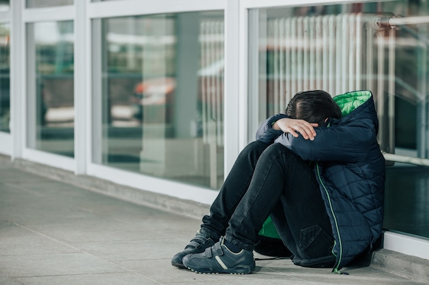 Mały chłopiec lub dziecko siedzą samotnie na podłodze przed szkołą po znęcaniu się