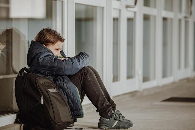 Mały chłopiec lub dziecko w wieku szkolnym siedzi samotnie na podłodze przed szkołą po znęcaniu się