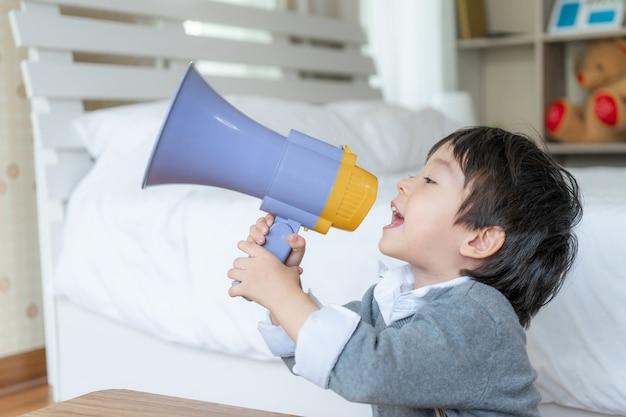 Mały chłopiec lubi rozmawiać z megafonem