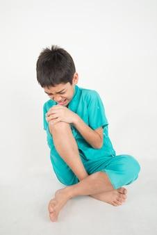 Mały chłopiec ma bóle nóg od bólów mięśni na kolanie