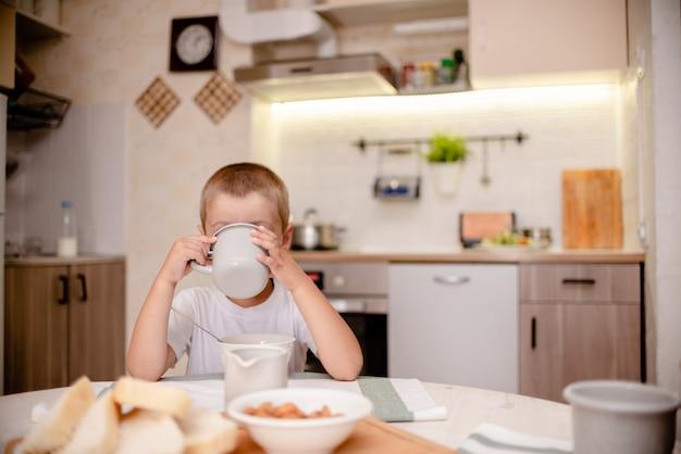 Mały chłopiec ma śniadanie. lekka kuchnia, drewniany stół i personel kuchenny