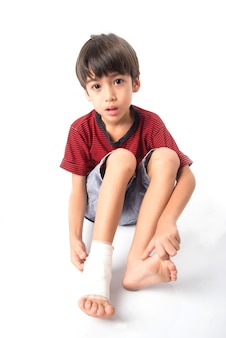 Mały chłopiec ma wypadek z nogą, która potrzebuje opatrunku w celu udzielenia pierwszej pomocy