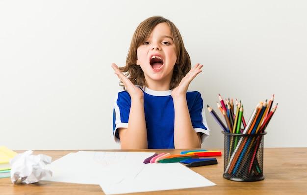 Mały chłopiec malowanie i odrabiania lekcji na biurku zaskoczony.