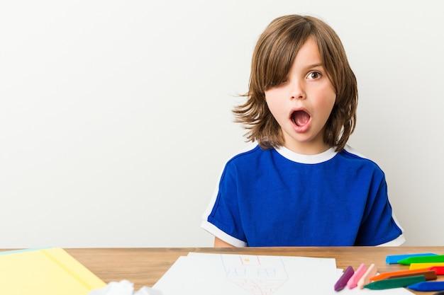Mały chłopiec malowanie i odrabianie lekcji na biurku jest zszokowany.