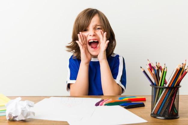 Mały chłopiec malowanie i odrabianie lekcji na biurku krzyczy podekscytowany do przodu.