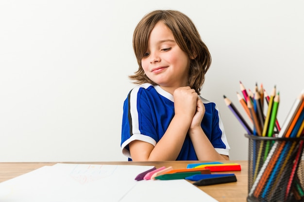 Mały chłopiec malowanie i odrabianie lekcji na biurku przestraszony i przestraszony.