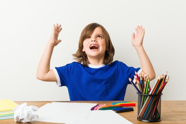 Mały chłopiec malowanie i odrabianie lekcji na jego biurku krzyczy do nieba.
