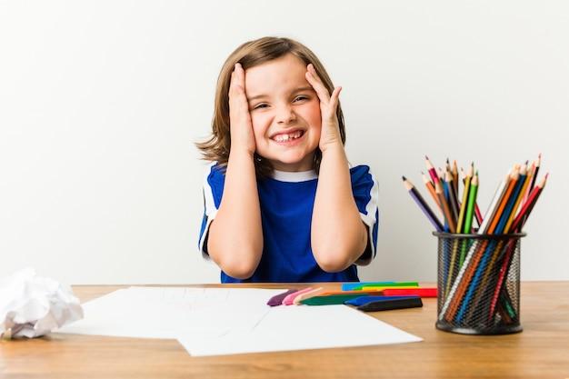 Mały chłopiec malowanie i odrabianie lekcji na jego biurku śmieje się radośnie trzymając ręce na głowie.