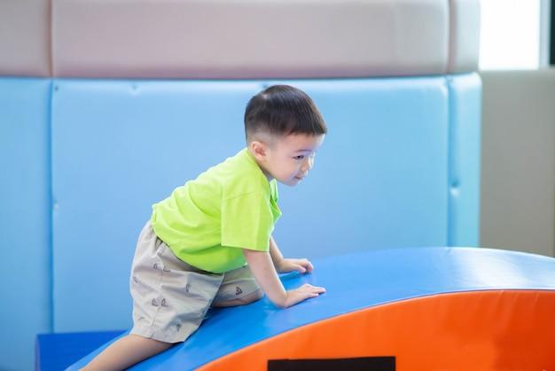 Mały chłopiec maluch, poćwiczyć w sali gimnastycznej ćwiczenia