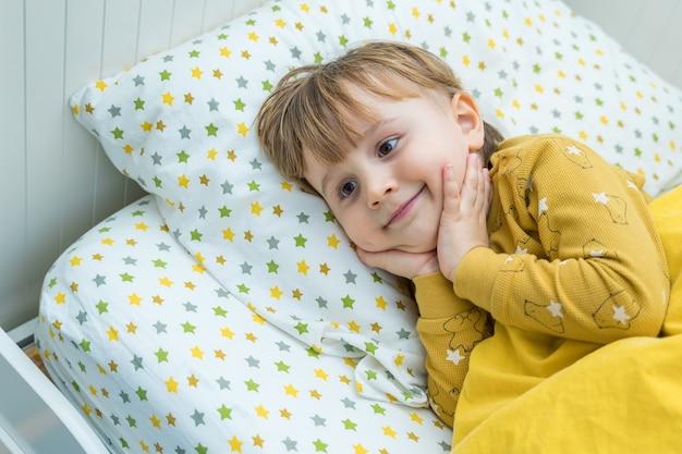 Mały chłopiec malucha leży w łóżku. dziecko budzi się rano z uśmiechem. szczęśliwy dzieciak odpoczywa w domu.