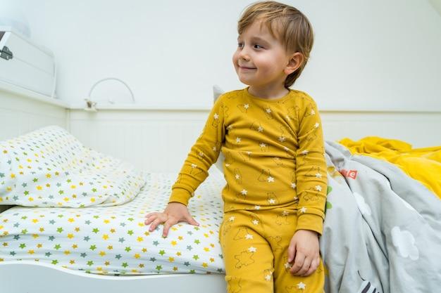 Mały chłopiec malucha siedzi w łóżku. dziecko budzi się rano z uśmiechem. szczęśliwy dzieciak odpoczywa w domu.