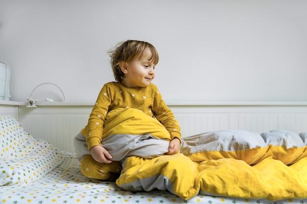 Mały chłopiec malucha siedzi w łóżku. dziecko budzi się rano.