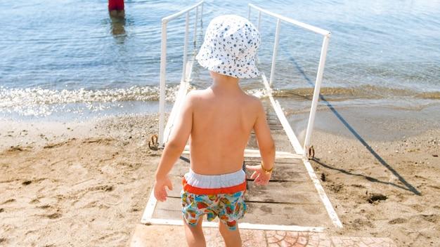 Mały chłopiec malucha w kapeluszu spaceru w wodzie morskiej na plaży.