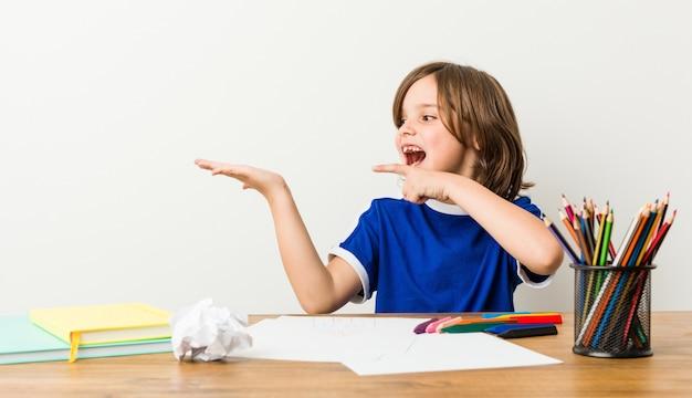 Mały chłopiec maluje i odrabia lekcje na biurku podekscytowany.