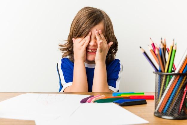Mały chłopiec maluje i odrabia lekcje na biurku, zasłania oczy rękami.