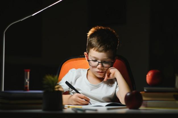 Mały chłopiec maluje późnym wieczorem w ciemnym pokoju