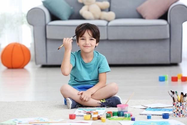 Mały chłopiec maluje siedząc na podłodze w pomieszczeniu
