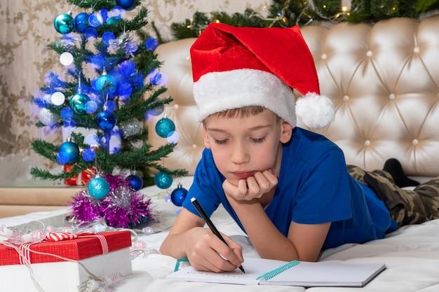 Mały chłopiec marzy o prezentach i napisaniu listu do świętego mikołaja w domu, wielokolorowy bokeh, czerwone pudełko