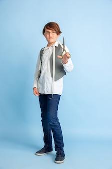 Mały chłopiec marzy o przyszłym zawodzie krawcowej. koncepcja dzieciństwa, edukacji i marzeń. chce odnieść sukces w branży modowej i stylistycznej, atelier, szyje ubrania. copyspace.