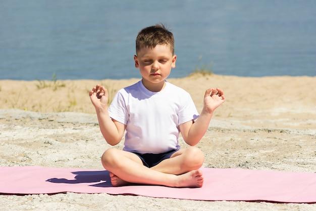 Mały chłopiec medytuje trzymając palce w pozie jogi z zamkniętymi oczami, siedząc na macie na plaży
