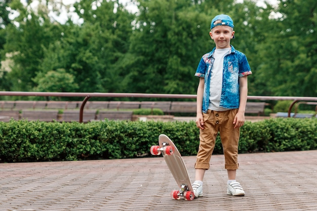 Mały chłopiec miejski i deskorolka. młody chłopak jedzie na deskorolce parka