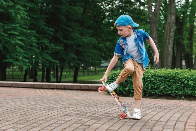 Mały chłopiec miejski i deskorolka. młody chłopak jedzie w parku na deskorolce