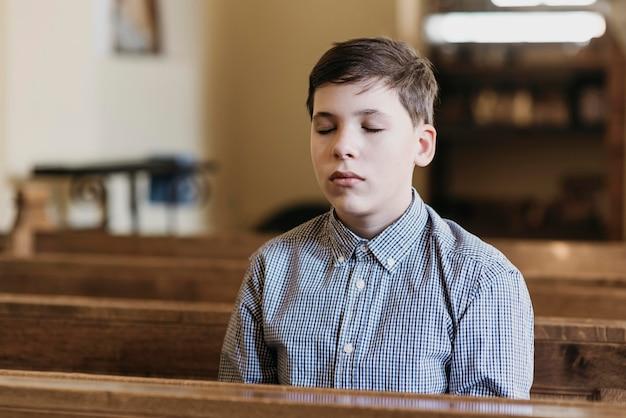 Mały chłopiec modlący się w kościele z zamkniętymi oczami