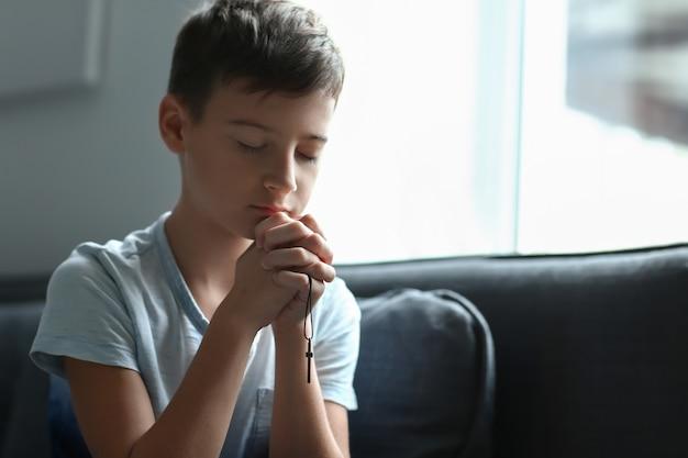 Mały chłopiec modli się w domu