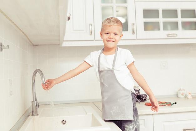 Mały chłopiec myje ręce w domowej kuchni