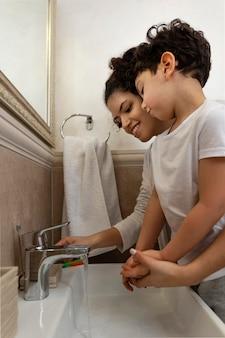 Mały chłopiec myje ręce z mamą