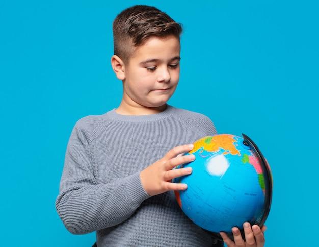 Mały chłopiec myślący wyrażenie i trzymający model mapy świata