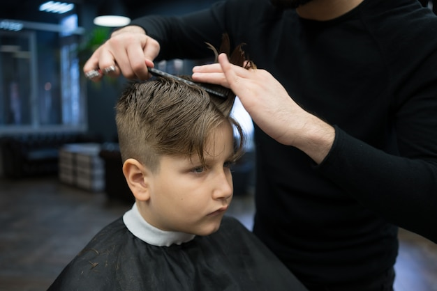 Mały chłopiec na fryzurę w fryzjera siedzi na krześle.