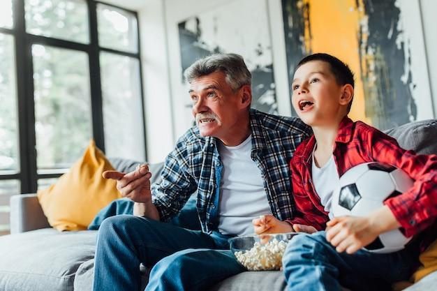 Mały chłopiec na kanapie z dziadkiem, dopingujący mecz futbolowy i trzymający piłkę futbolową ..