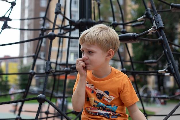 Mały chłopiec na placu zabaw jest zdenerwowany. jest smutny, będzie płakał